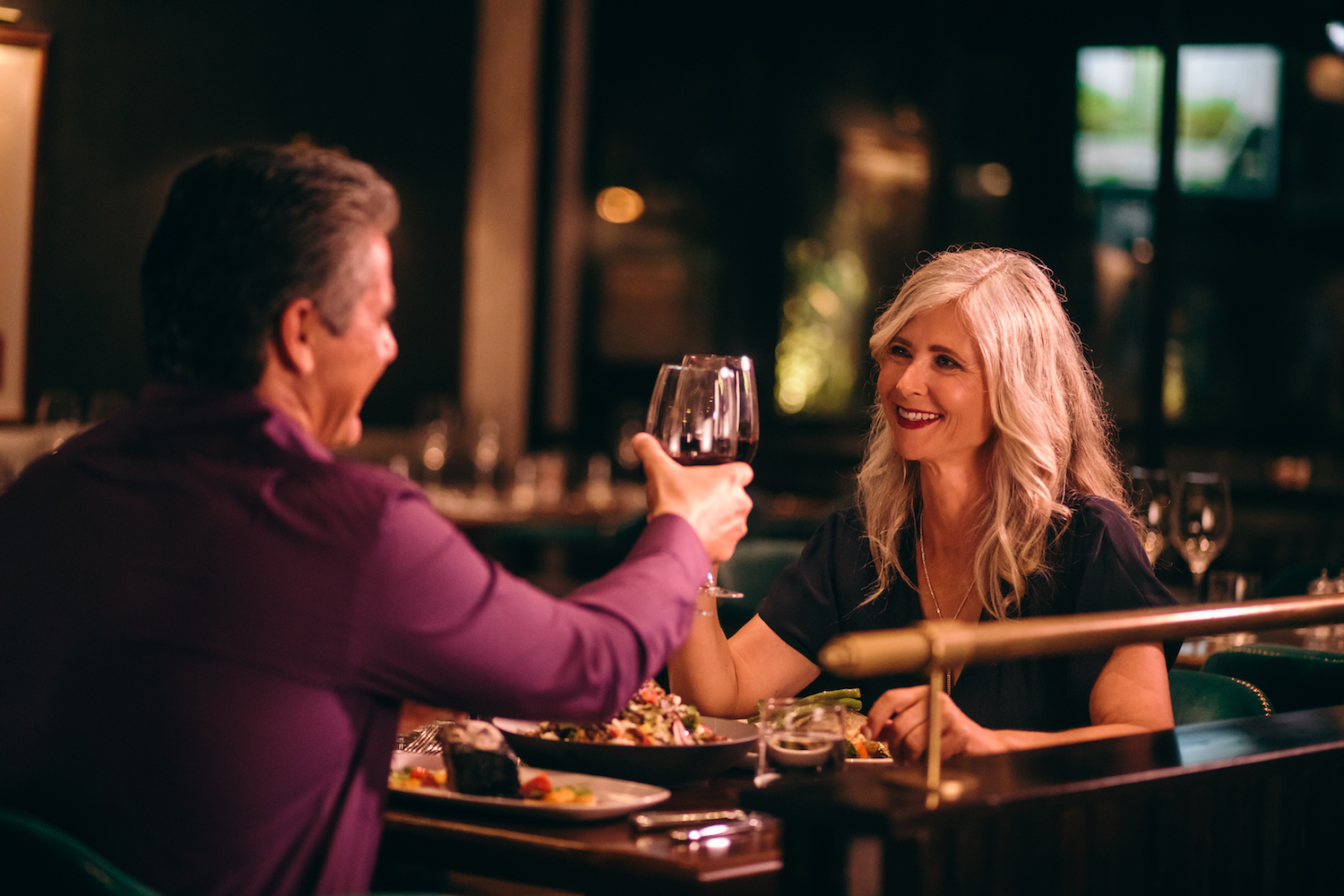 Senior couple in love toasting with red wine and having dinner at fine dining restaurant